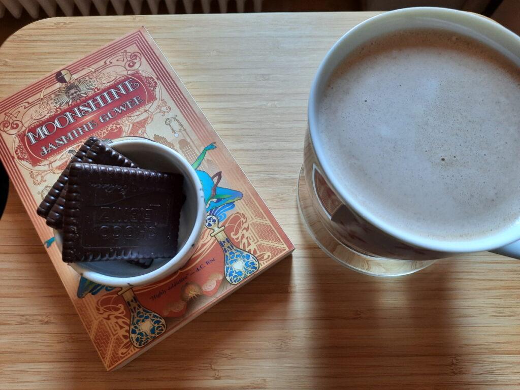 """Die Taschenbuchausgabe von """"Moonshine"""", auf der eine kleine Schale steht, in der drei Schokoladen-Butterkekse liegen, rechts davon eine große Tasse, die mit Milchkaffee gefüllt ist."""