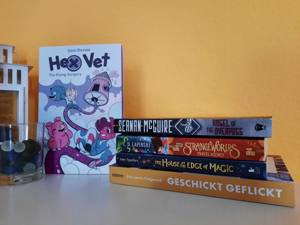"""Ein Stapel aus vier Büchern vor einer orangen Wand auf der rechten Seite, links steht der Comic """"Hex Vet 2) neben dem Buchstapel, so dass das Cover zu sehen ist."""