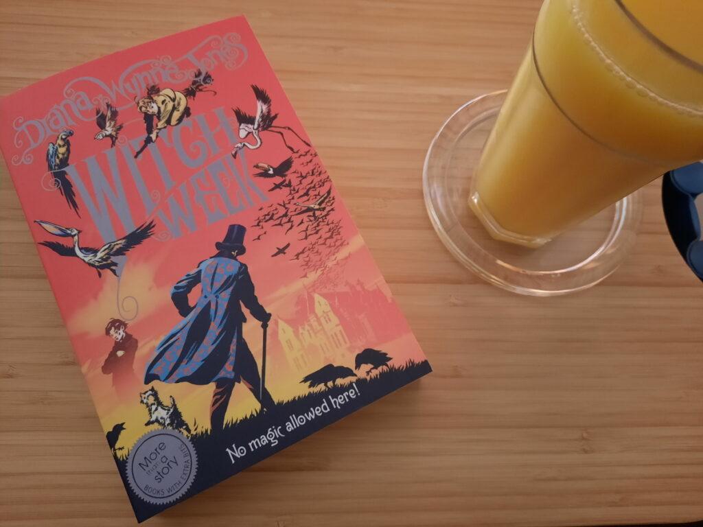 """Links liegt die englische Taschenbuchausgabe von """"Witch Week"""" (mit dem Titelzusatz """"No Magic Allowed Here!"""", rechts von dem Buch steht ein Glas mit Orangensaft."""