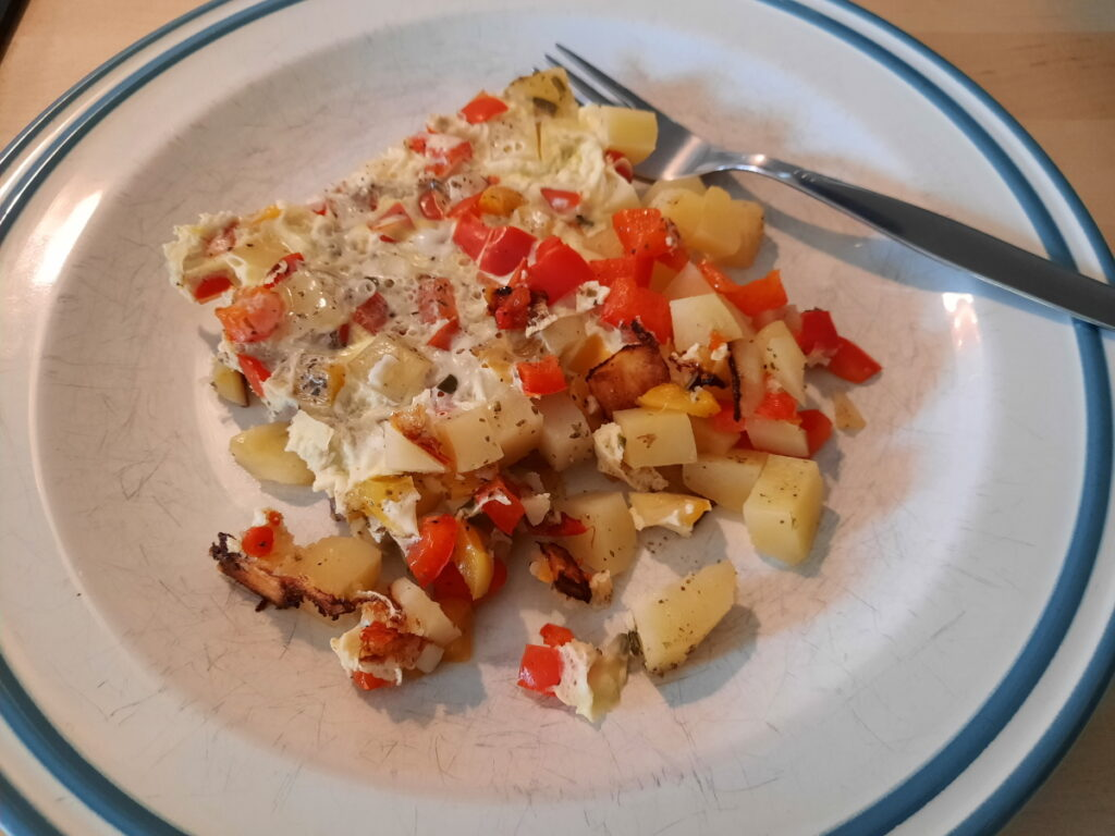 Ein - etwas unordentlich auf dem Teller gelandetes - Omelett mit Kartoffel- und Paprikastückchen.