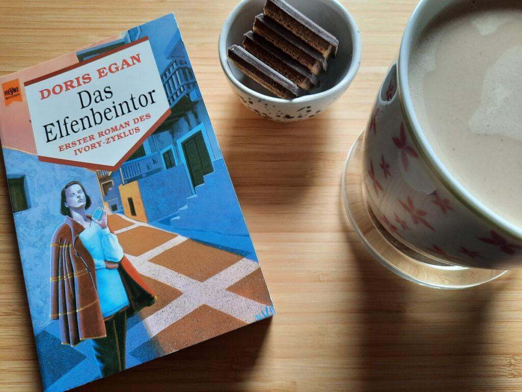 """Links ein Buch mit altmodischem SF-Cover und dem Titel """"Das Elfenbeintor"""", rechts kann man eine große Tasse mit Milchkaffee erahnen und dazwischen steht eine kleine Schale mit vier Schokowaffeln."""