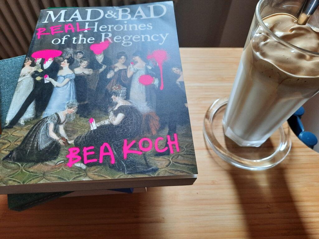 """Links ein Buchstapel, auf dem oben der Titel """"Mad and Bad - Real Heroines of the Regency"""" von Bea Koch zu sehen ist. Rechts ein großes Glas mit Dalgona-Kaffee."""