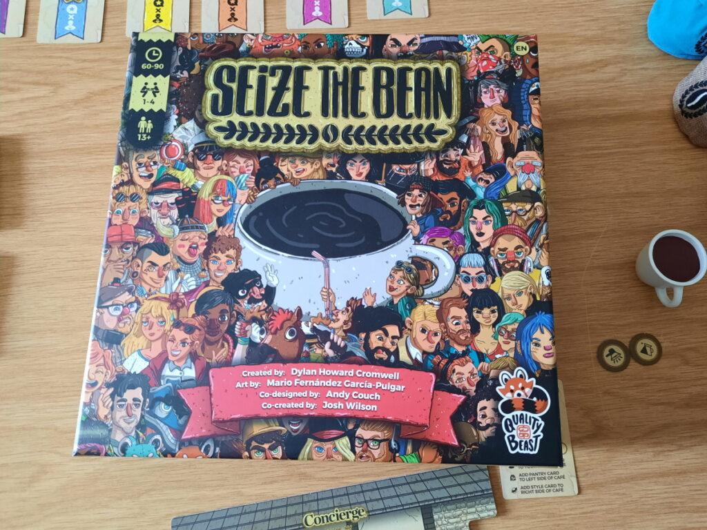 """Der Karton des Brettspiels """"Seize the Bean"""" - auf dem Covers ieht man eine riesige Kaffeetasse und eine sehr unterschiedliche Gruppe von Menschen, die sich drumherum drängeln."""