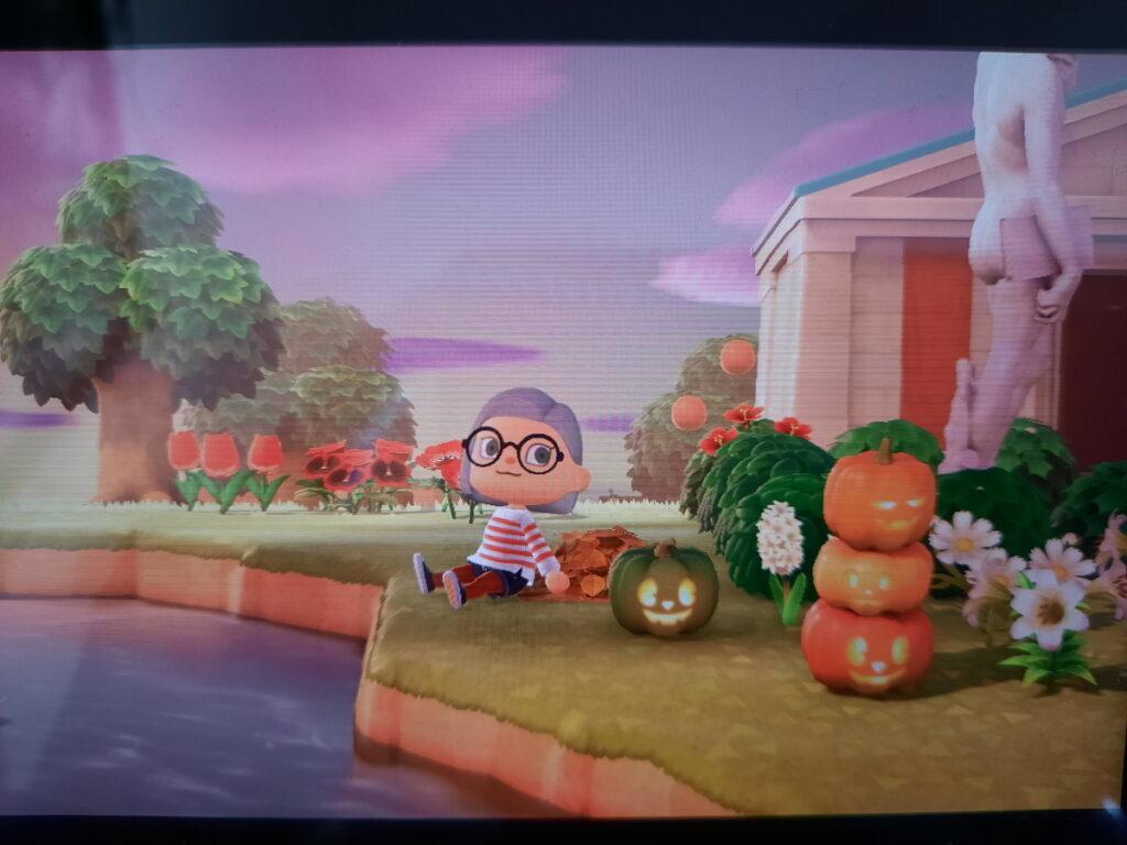 Animal-Crossing-Screenshot, der meinen Charakter in einem Ringelpulli und einer schwarzen Jeans zeigt, während er auf einem rot-orangem Laubhaufen sitzt. Daneben sind zwei brennende Kürbis-Laternen zu sehen und im Hintergrund zeigt der Himmel schon die ersten Dämmerungsfarben.