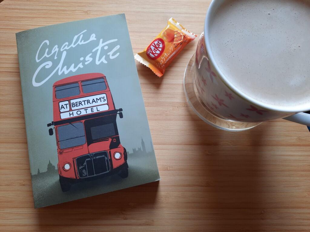 """Links die Taschenbuchausgabe von """"At Bertram's Hotel"""", rechts eine große Tasse mit Milchkaffee und dazwischen liegt ein kleines japanisches KitKat (Geschmacksrichtung Schoko-Orange)"""