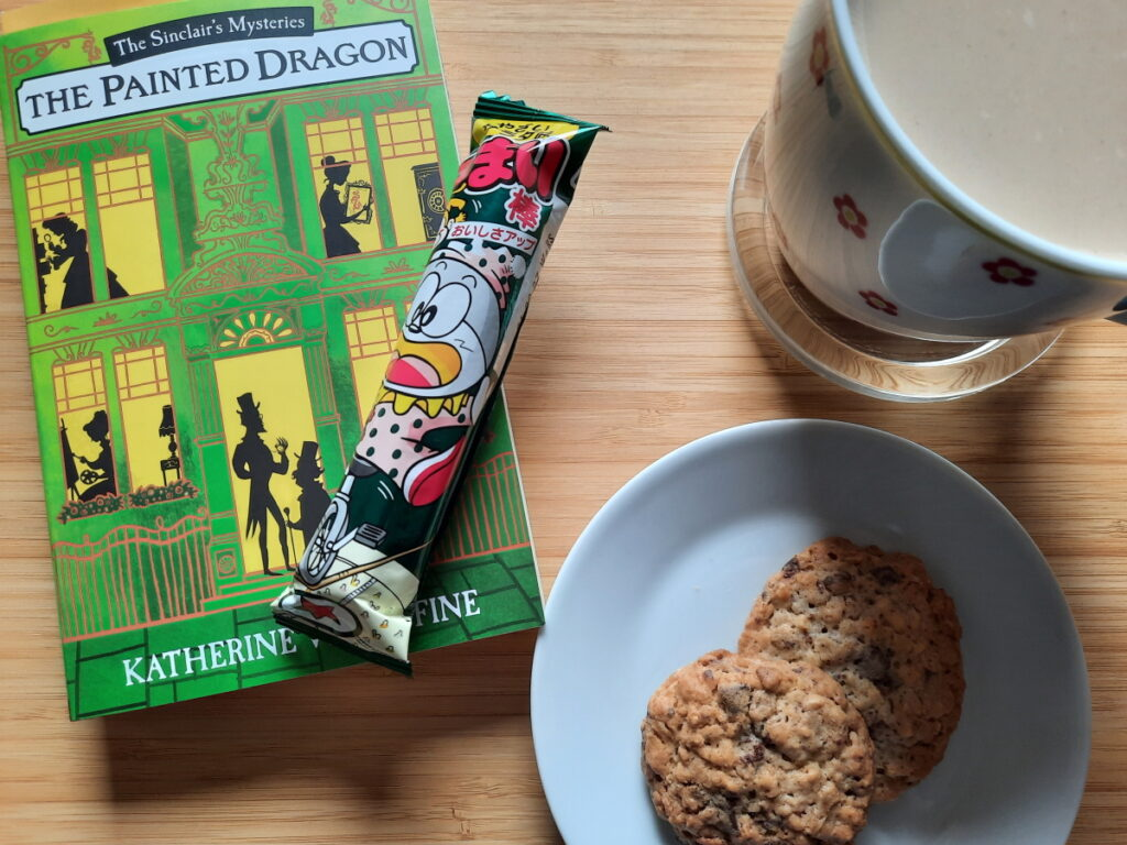 """Links die Taschenbuchausgabe von """"The Painted Dragon"""" von Katherine Woodfine, darauf ein verpackter Umai-bo, rechts oben eine große Tasse mit Milchkaffee, darunter ein kleiner Teller mit zwei Haferflocken-Keksen."""