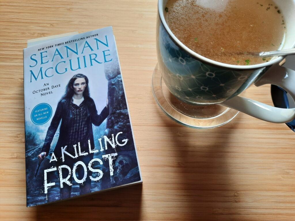 """Links die Taschenbuchausgabe von """"A Killing Frost"""", rechts eine große Tasse mit Gemüsebrühe"""