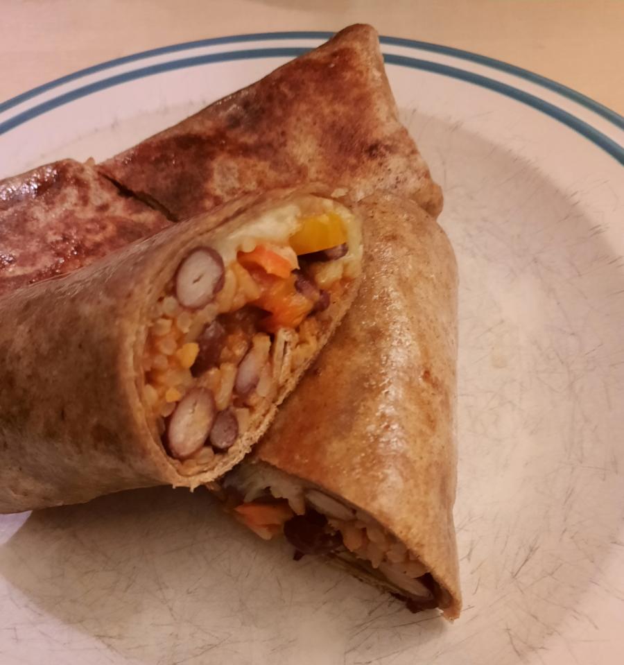 Ein Teller mit zwei Wraps, einer davon ist durchgeschnitten und der Anschnitt zeigt eine Füllung aus Reis, Kidney-Bohnen, Paprika und Zwiebeln.