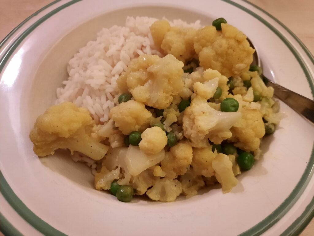 Ein tiefer Teller, der mit Reis und einer Mischung aus Reis und Erbsen (gewürzt mit Zwiebeln, Knoblauch und Curry) gefüllt ist.