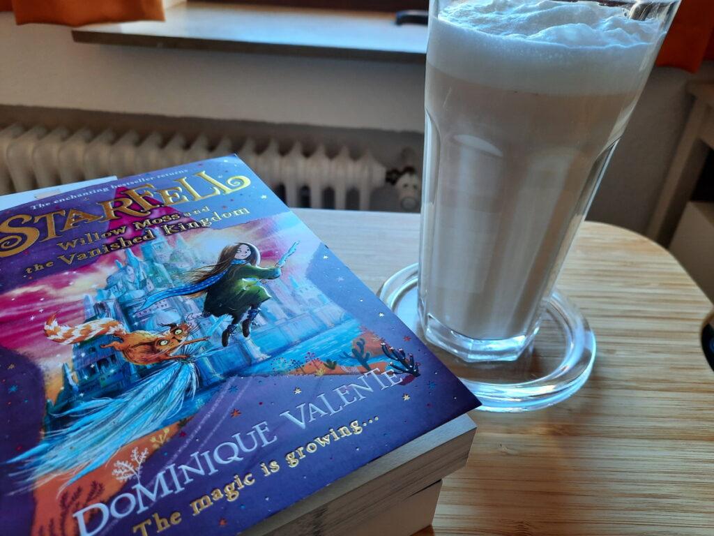 """Links wieder die Taschenbuchausgabe von """"Willow Moss and the Vanished Kingdom"""", rechts ein großes Glas mit Chai-Milchtee, das von einer Milchschaumhaube gekrönt wird."""