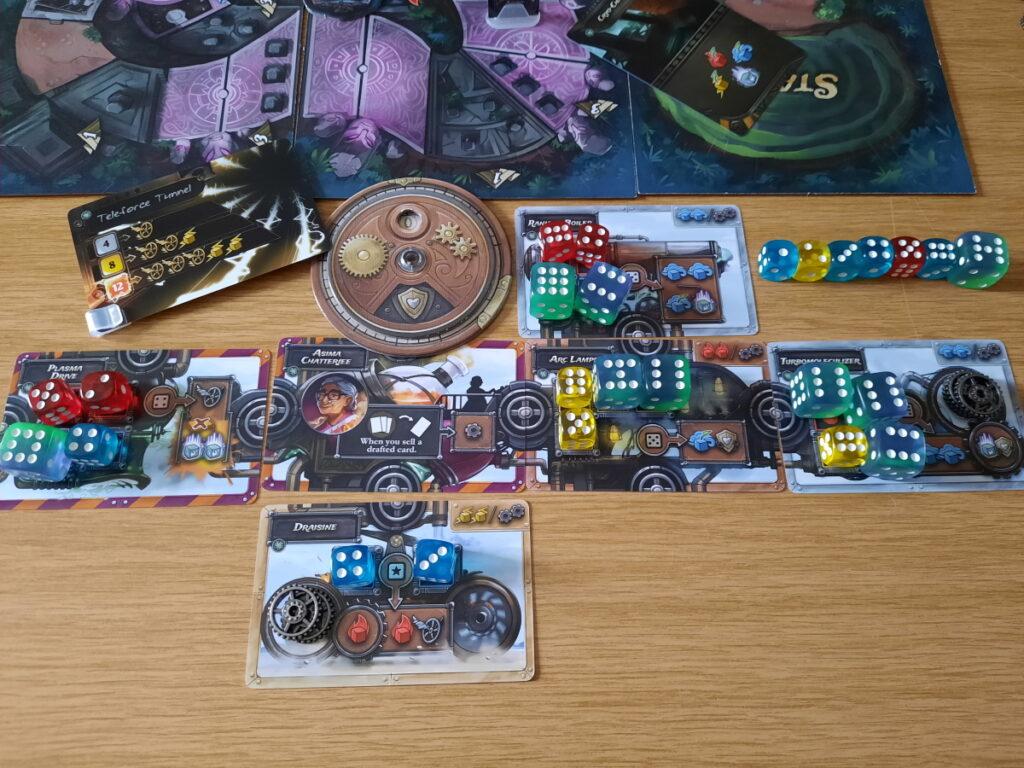 """Ein Blick auf den Endstand meiner Steampunk-Rally-Maschine. Die """"Maschine"""" besteht aus mehreren Karten, deren spielbare Slots alle mit Würfeln ausgefüllt sind. Außerdem ist eine Scheibe zu sehen, die keinerlei Schaden an der Maschine meldet und eine Würfelreihe, deren Punkte von 1 bis 7 gehen."""
