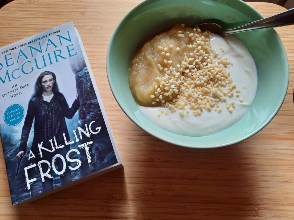 """Links die Taschenbuchausgabe von """"A Killing Frost"""", rechts eine grüne Schale mit Vanillequark, Apfelmus und Mandelsplittern."""