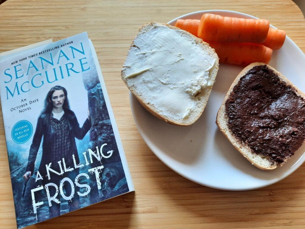 """Links """"A Killing Frost"""", rechts ein Teller mit einem aufgeschnittenen Brötchen (eine Hälfte mit Frischkäse, die andere mit Zartbittercreme) und drei Möhren."""