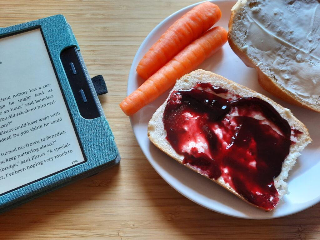 """Links ein angeschalteter eReader, der den Anfang des achten Kapitels von """"Scales and Sensibility"""" zeigt, rechts ein Teller mit einem Brötchen (die eine Hälfte mit Brombeergelee, die andere mit Frischkäse bestrichen) und zwei Möhren."""