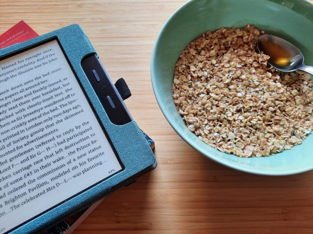 Links ein angeschalteter eReader, rechts eine grüne Schale mit Porridge, darin liegt ein Löffel mit Honig.