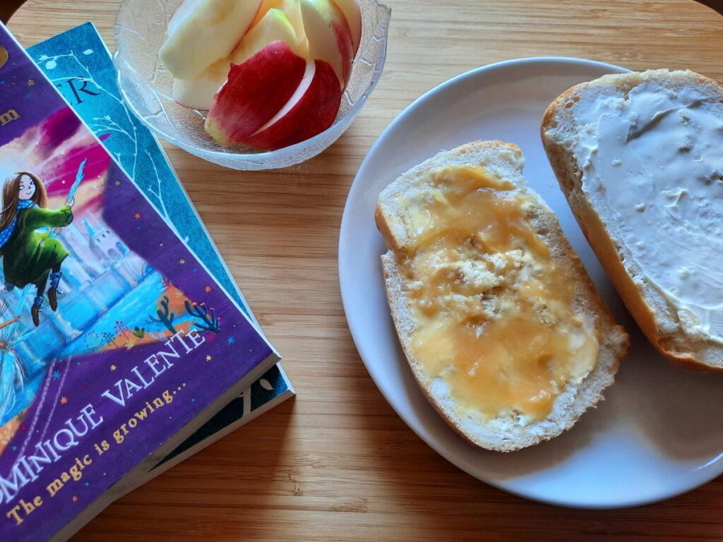 Links ein Stapel aus zwei Taschenbüchern, es lässt sich gerade so erahnen, dass der obere Titel von Dominique Valente ist. Rechts ein Teller mit zwei Brötchenhälften, die eine mit Honig, die andere mit Frischkäse. Dazwischen steht am oberen Rand des Fotos eine Glasschale mit Apfelspalten.