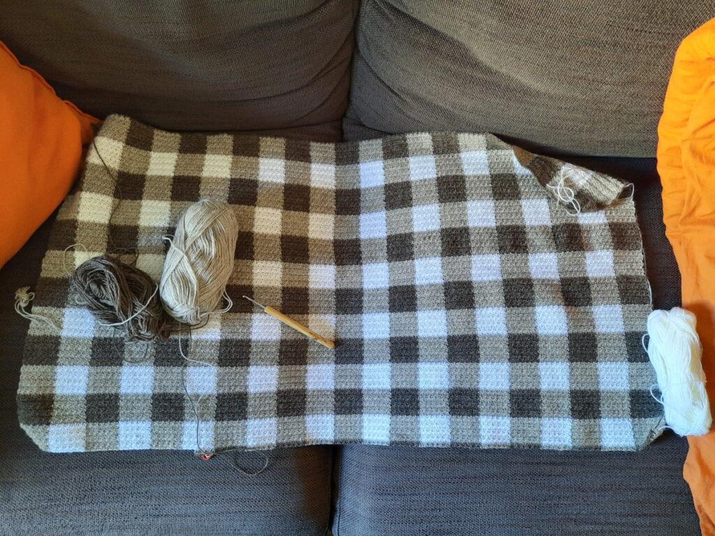 Ein Stück einer braun-weiß-karierten Häkeldecke, die auf einem braunen Sofa liegt und darauf zwei Wollknäule und eine Häkelnadel.
