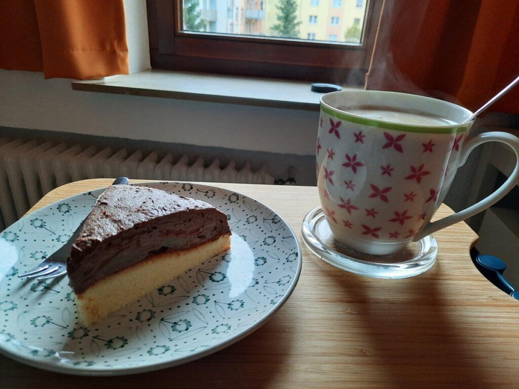 Links ein Teller mit einem Stück Schokosahne-Birnen-Torte, rechts eine große, dampfende Tasse mit Milchkaffee.