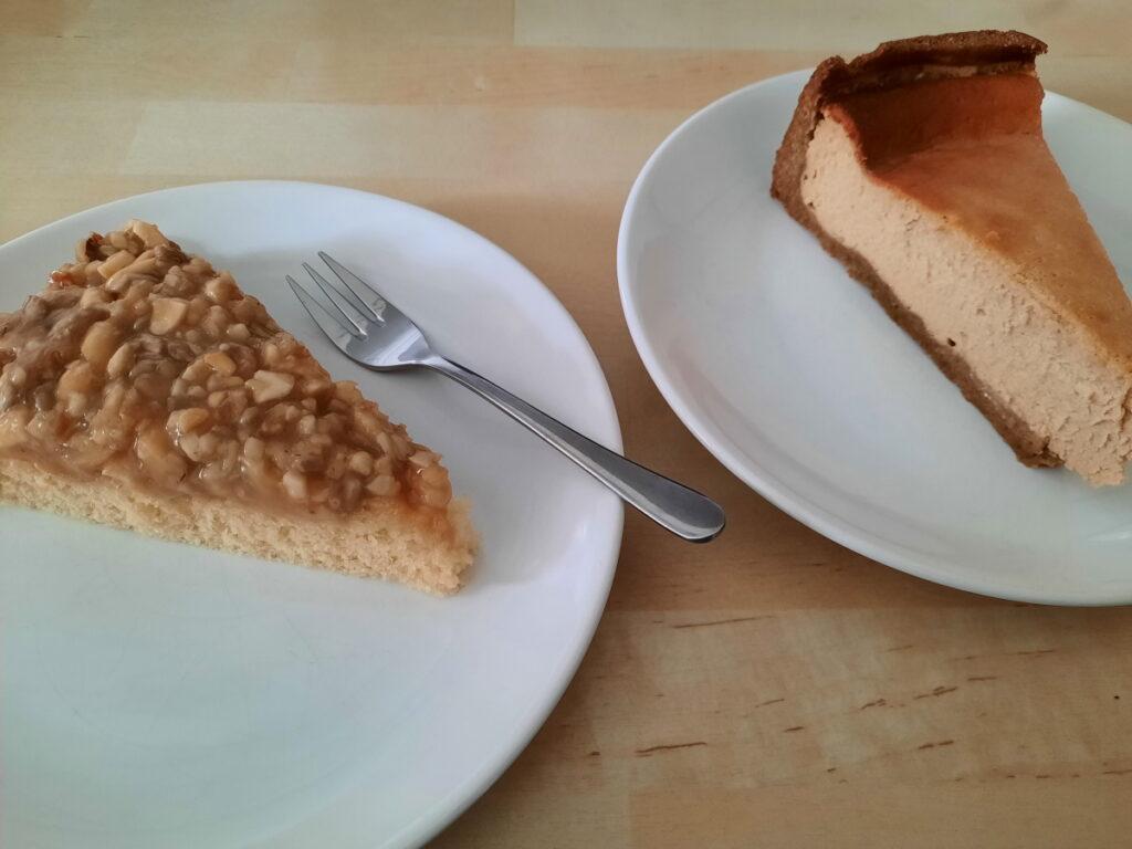 Zwei Teller, auf denen jeweils ein Stück Kuchen liegt. Links ein Stück Nuss-Karamell-Kuchen (ein fester Boden, der mit einer Nuss-Karamell-Schicht überzogen wurde), rechts ein Stück Kaffee-Käsekuchen.