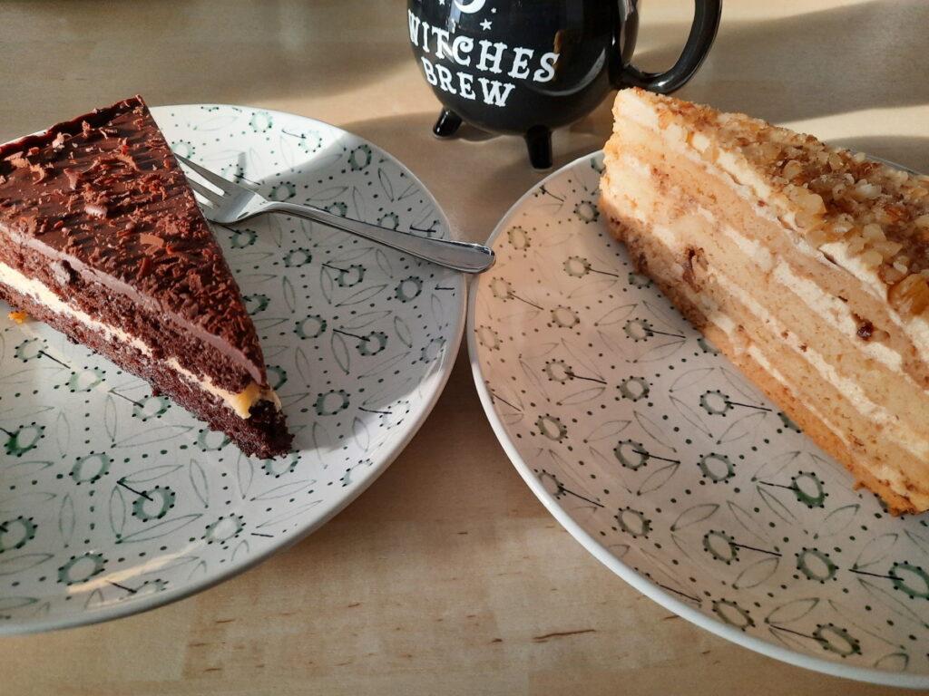 Zwei Teller mit Kuchen, links ein Stück Schoko-Pudding-Torte, rechts ein Stück Honig-Mandel-Torte, dazwischen steht eine wie ein Hexenkessel geformt Tasse mit Milchtee.