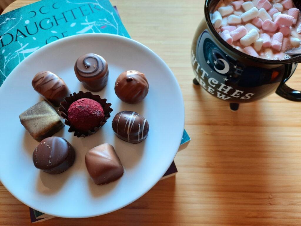 Links eine Untertasse mit acht unterschiedlichen Pralinen, rechts eine Tasse, die wie ein Hexenkessel geformt ist und die mit Kakao und Mini-Marshmallows gefüllt ist.