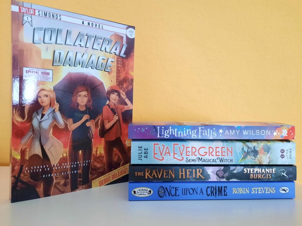 """Links das Taschenbuch von """"Collateral Damage"""" mit dem Cover zum Betrachter aufgestellt, rechts davon ein kleiner Stapel mit (von unten nach oben) """"Once Upon a Crime"""", """"The Raven Heir"""", """"Eva Evergreen"""" und """"Lightning Falls""""."""