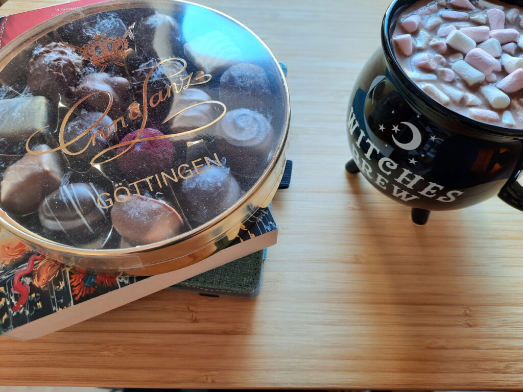 """Links eine Schachtel mit einer Pralinenmischung, die auf einem Buch steht, rechts eine schwarze Tasse, die aussieht wie ein Kessel auf vier Füßen, und die Aufschrift """"Witches Brew"""" trägt."""