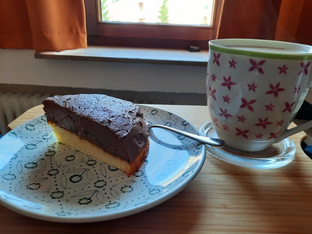 Links ein grüngemusterter Teller mit einem Stück Torte (Schokoladensahne und Birnen auf einem hellen Bisquitboden), rechts eine große Tasse Milchkaffee.