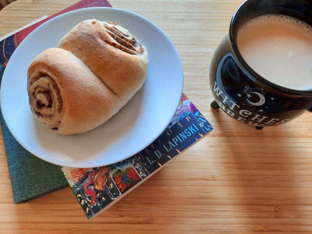 Links ein Hefeteilchen auf einer Untertasse, rechts eine an einen Hexenkessel-erinnernde Tasse mit schwarzem Tee mit Milch