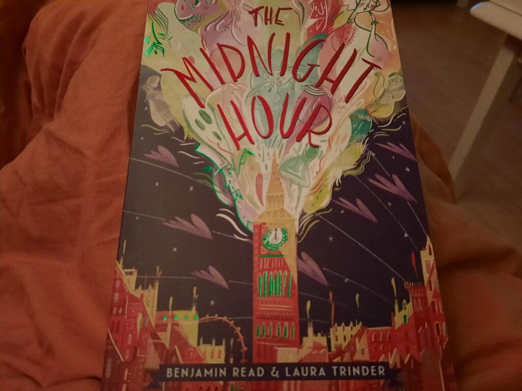 """Das Taschenbuch von """"The Midnight Hour"""" auf meiner orangen Sofadecke."""